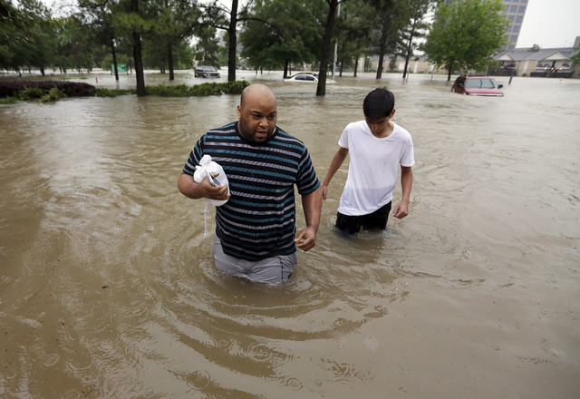 Darius Simon, left, and his son Isaac Hernandez wade through floodwaters as they try to reach Simon's mother to rescue her from her flooded apartment Monday, April 18, 2016, in Houston. Storms hav ...