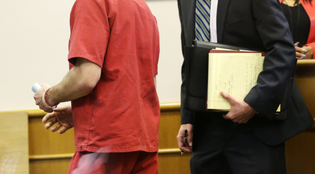 John Charlton, left, the man accused of dismembering a woman in her suburban home and dumping her body parts in Seattle recycling bins, is viewed through a window as he walks with one of his attor ...