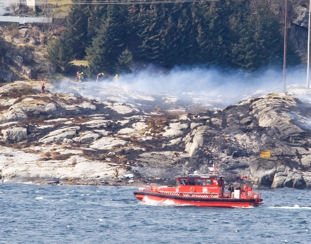 A search and rescue vessel patrols off the coast of the island of Turoey, near Bergen, Norway, as emergency workers attend the scene after a helicopter crashed believed to be have 13 people aboard ...