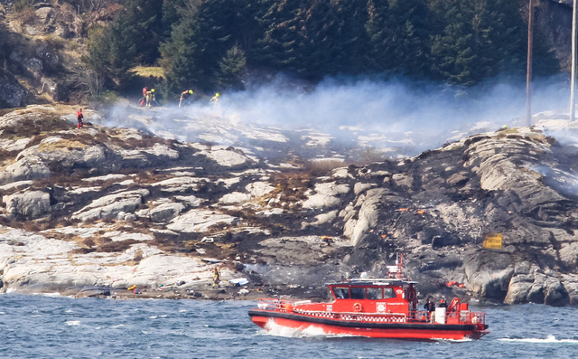 A search and rescue vessel patrols off the island of Turoey, near Bergen, Norway, as emergency workers attend the scene of a helicopter crash believed to have 13 people aboard, Friday April 29, 20 ...