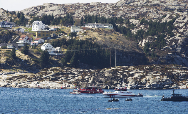 A search and rescue vessel patrols off the island of Turoey, near Bergen, Norway, as emergency workers on the shoreline attend the scene after a helicopter crashed believed to be have 13 people ab ...