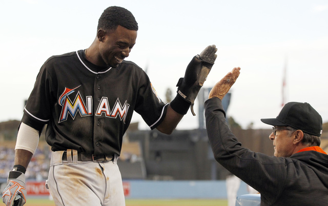 In this April 27,. 2016 file photo, Miami Marlins' Dee Gordon, left, gets congratulations from manager Don Mattingly after scoring on a single by Giancarlo Stanton during the first inning of a bas ...