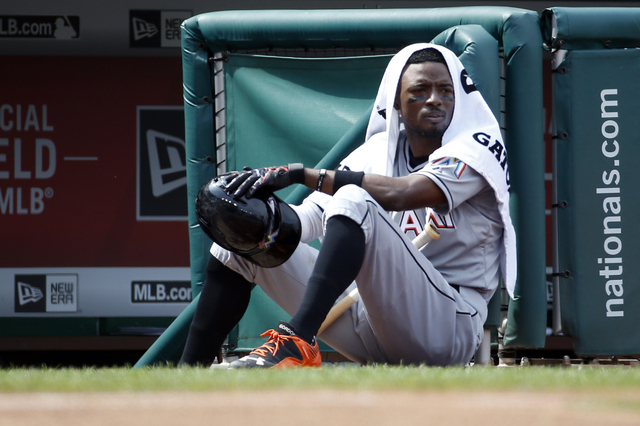 In this Aug. 30, 2015 file photo, Miami Marlins second baseman Dee Gordon (9) sits on the edge of the dugout during a baseball game against the Washington Nationals at Nationals Park, in Washingto ...