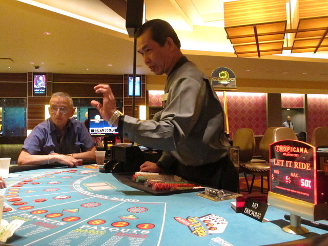 In this March photo, dealer Thayn Pham conducts a card game at the Tropicana casino in Atlantic City, N.J.  (Wayne Parry/Associated Press)