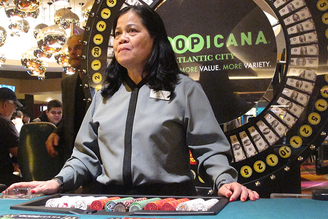 This March 9, 2016 photo shows Hat Nguyen, a dealer at the Tropicana casino in Atlantic City N.J., waiting for customers to place bets at a cash wheel. On Friday April 29, 2016, the Casino Associa ...