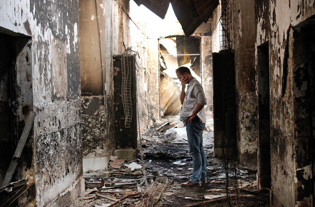 An employee of Doctors Without Borders walks inside the charred remains of the organization's hospital after it was hit by a U.S. airstrike in Kunduz, Afghanistan, Oct. 16, 2015. (Najim Rahim/AP)
