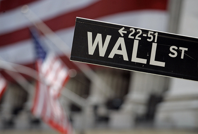FILE - This May 11, 2007 file photo shows a Wall Street sign in front of the flag-draped facade of the New York Stock Exchange. Global stock markets mostly fell Friday, April 29, 2016,  after Wall ...