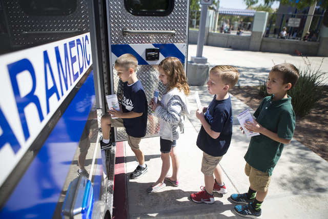 Gavin Buenrustro, from left, 6, Kate Milmeister, 7, Layton Bachhuber, 6, and Matthew Kleiner, 7, line up to tour an ambulance during a 911 Education Month event at Glen Taylor Elementary School on ...