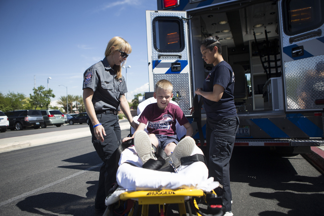 Melanie Bangle, from left, paramedic for Community Ambulance, with the help of her son Jacob Dennon, 9, and  supply technician Melissa Valencia, demonstrate how to transport a person in a gurney d ...
