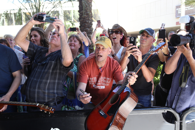 Tim Benge reaches his guitar out to get signed by members of the Eli Young Band outside the 51st Academy of Country Music Awards Sunday, April 3, 2016, at the MGM Grand in Las Vegas.  (Rachel Asto ...