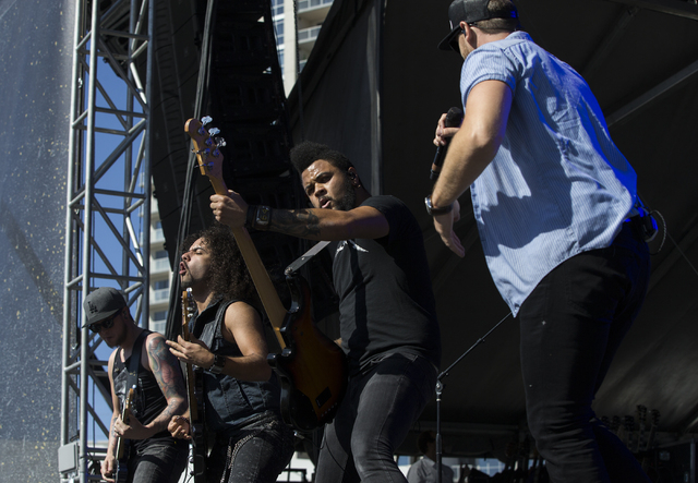 "Chase Rice, right, and his band perform during the last day of the American Country Music's ""Party for a Cause,"" event at the Las Vegas Festival Grounds on Sunday, April 3, 2016  ..."
