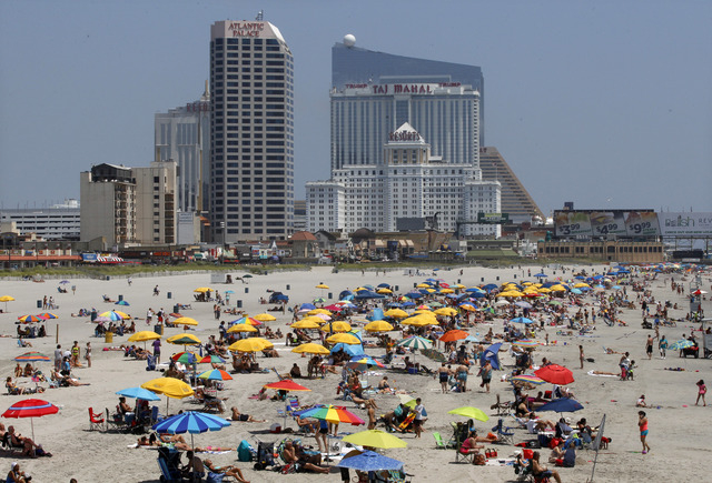 With Atlantic Palace Suites Hotel, Resorts Casino Hotel, Trump Taj Mahal Casino Hotel and Revel Casino in the background, people relax on the beach Wednesday, July 23, 2014, in Atlantic City, N.J. ...