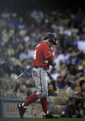 Washington Nationals' Bryce Harper kisses a medal around his neck before batting in the second inning of their baseball game against the Los Angeles Dodgers, Saturday, April 28, 2012, in Los Angel ...