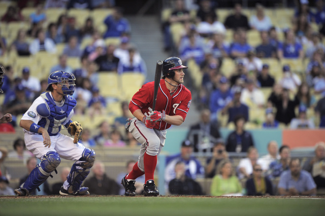 Washington Nationals outfielder Bryce Harper taps back to the pitcher in the first at-bat of his major league career, in front of Dodgers catcher A.J. Ellis, on April 28, 2012, in Los Angeles. Fou ...
