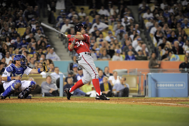 Washington Nationals' Bryce Harper hits a double as Los Angeles Dodgers catcher A.J. Ellis looks on during the seventh inning of their baseball game against the Los Angeles Dodgers, Saturday, Apri ...
