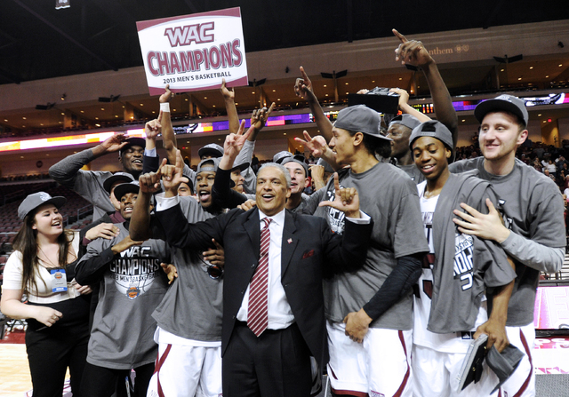 New Mexico State coach Marvin Menzies, center, celebrates with his team after defeating UT Arlington in the Western Athletic Conference tournament championship NCAA college basketball game, Saturd ...