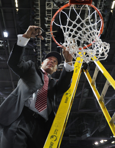 New Mexico State coach Marvin Menzies cuts down the net after his team's victory over UT Arlington in their Western Athletic Conference tournament championship NCAA college basketball game, Saturd ...