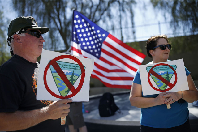 David Andersen, left, and Kaylene Andersen, of Overton, Nev., hold signs during a rally in support of rancher Cliven Bundy outside of the federal courthouse Friday, April 22, 2016, in Las Vegas. A ...