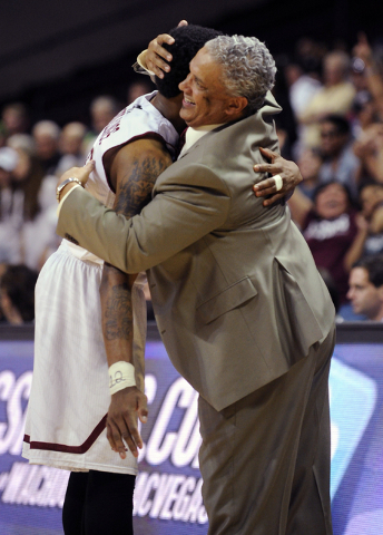 New Mexico State's Daniel Mullings, left, is hugged by coach Marvin Menzies after their team defeated Idaho 77-55 for the championship of the Western Athletic Conference tournament, in an NCAA col ...