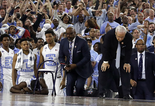North Carolina head coach Roy Williams, right and his players on the bench react after the NCAA Final Four tournament college basketball championship game against Villanova, Monday, April 4, 2016, ...