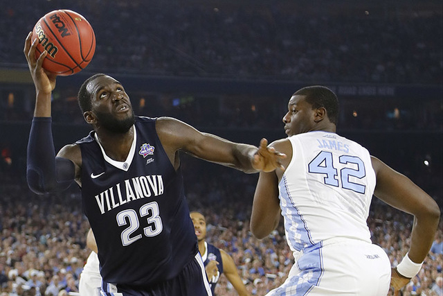 Villanova forward Daniel Ochefu (23) shoots by North Carolina forward Joel James (42) during the first half of the NCAA Final Four tournament college basketball championship game Monday, April 4,  ...