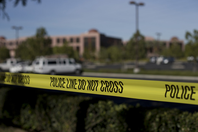 Yellow tape is strung around the Inland Regional Center, the site of last week's shooting rampage that killed 14 people, Tuesday, Dec. 8, 2015, in San Bernardino, Calif. Just days before Syed Faro ...
