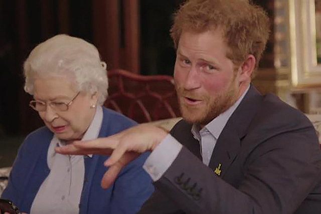 """This image taken from a video released by Kensington Palace, London, on Friday April 29, 2016 shows Queen Elizabeth II sitting with her grandson, Prince Harry as he says """"Boom"""" whilst receiving a  ..."""