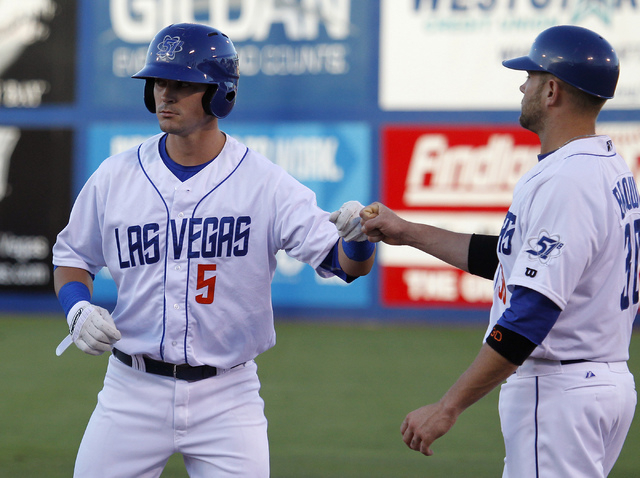 Las Vegas 51s shortstop Matt Reynolds (5) bumps fists with first base coach Andrew Brown after getting a hit against the El Paso Chihuahuas during their baseball game at Cashman Field in Las Vegas ...