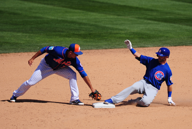 Chicago Cubs base runner Tommy La Stella slides safely into second base after hitting a double as New York Mets second baseman T.J. Rivera applies the tag in the sixth inning of their MLB preseaso ...