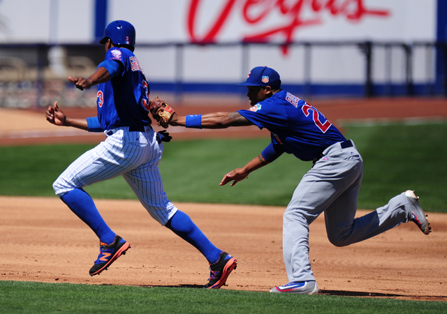 Chicago Cubs shortstop Addison Russell, right, tags out New York Mets base runner Curtis Granderson after Granderson was caught in a rundown  in the first inning of their MLB preseason baseball ga ...