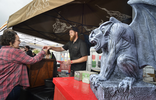Adam Quinn, center, hands a beer sample to a festival goer at the Stone Brewing company tent during the Great Vegas Festival of Beer in the 800 block of Fremont Street in Las Vegas on Saturday, Ap ...