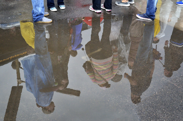 Festival goers are reflected in a puddle on a rainy afternoon during the Great Vegas Festival of Beer in the 800 block of Fremont Street in Las Vegas on Saturday, April 9, 2016. Bill Hughes/Las Ve ...