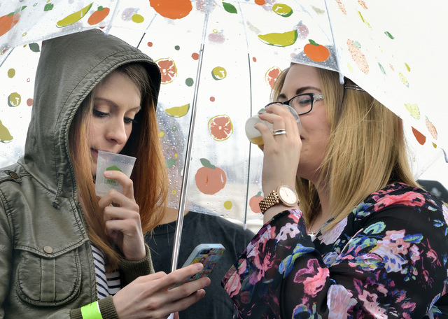 Sarah Knott, left, and Rachel Sodupe wait out the rain under an umbrella during the Great Vegas Festival of Beer in the 800 block of Fremont Street in Las Vegas on Saturday, April 9, 2016. Bill Hu ...