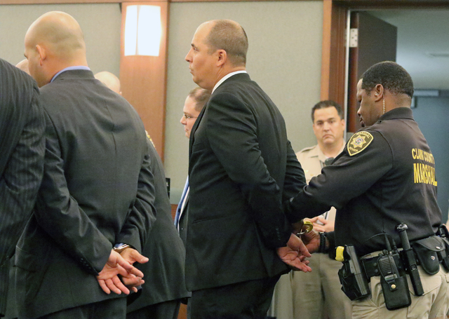 A marshal handcuffs Jeffrey Martin, who stands next to a handcuffed Mark Branco, left, in Judge Valerie Adair's courtroom at Regional Justice Center Tuesday, April 12, 2016, in Las Vegas. Martin,  ...
