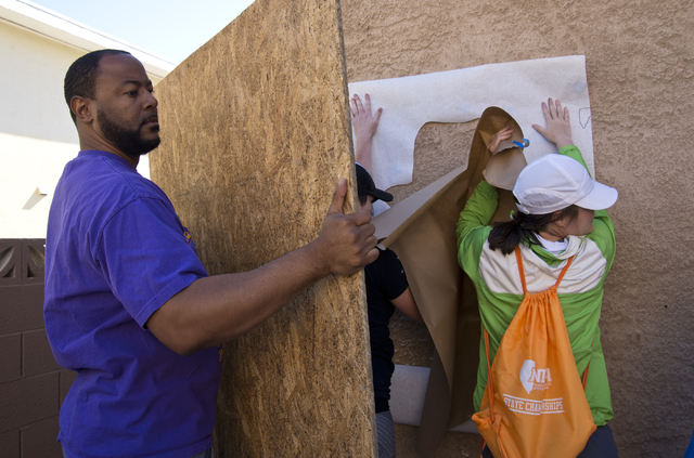 New Genesis Tranditional Housing executive director Maurice Page holds a board to block the wind during a volunteer event held by the Gaels Give Hope organization from Bishop Gorman High School, b ...