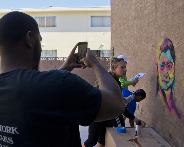 Brandon Russell, a resident at a New Genesis Transitional Housing apartment complex, takes a photo as the Gaels Give Hope organization from Bishop Gorman High School paints murals during a volunte ...