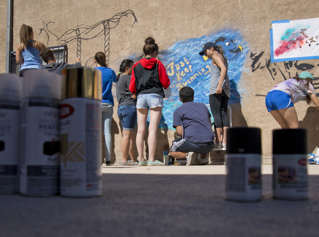 Students from Bishop Gorman High School work to paint a mural during a volunteer event held by the Gaels Give Hope organization, benefitting a New Genesis Transitional Housing apartment complex in ...