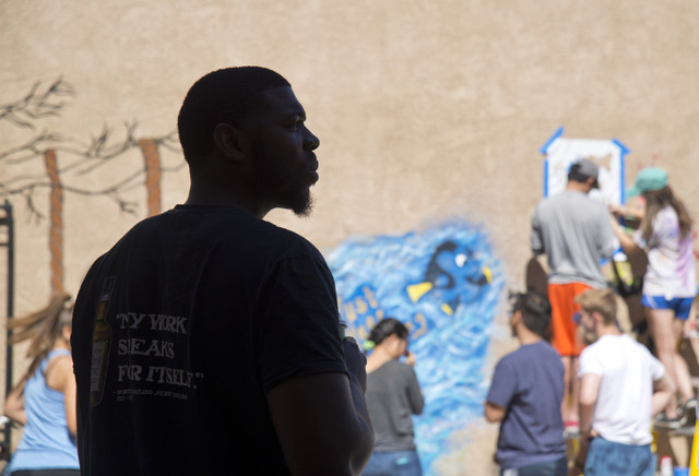 Brandon Russell, a resident at the New Genesis Transitional Housing apartment complex, watches as the Gaels Give Hope organization from Bishop Gorman High School paints murals during a volunteer e ...