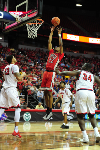 UNLV guard Patrick McCaw (22) goes up for a shot against Fresno State center Terrell Carter II (34) and forward Cullen Russo in the second half of their Mountain West Conference semifinal basketba ...