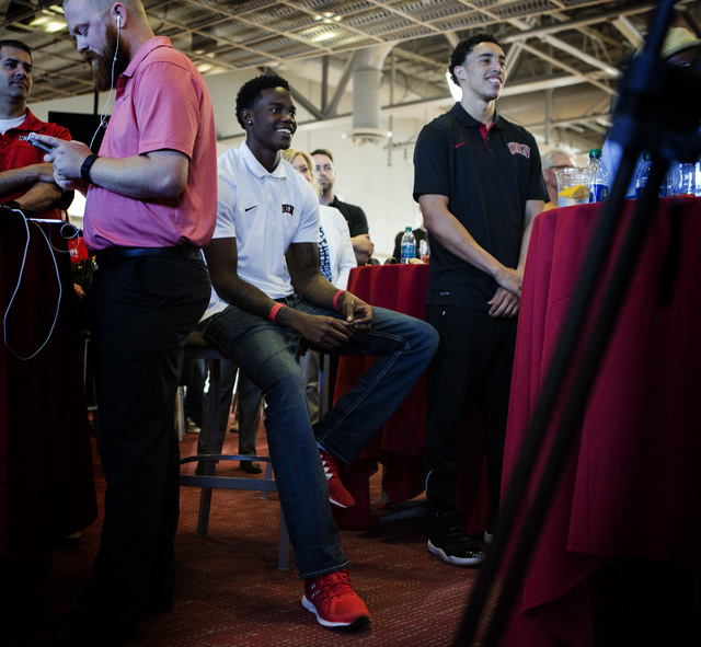 UNLV men's basketball players Dwayne Morgan, center, and Austin Starr,right, smile while new UNLV men's basketball coach Marvin Menzies speaks during a press conference at Mendenhall Center on Fri ...