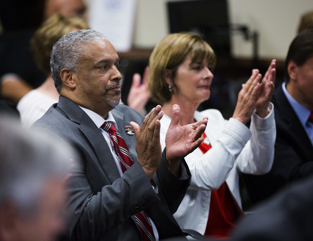 New UNLV men's basketball coach Marvin Menzies,left, and Tina Murphy-Kunzel applaud after the University of Nevada Board of Regents approved his contract on Friday, April 22, 2016. (Jeff Scheid/La ...