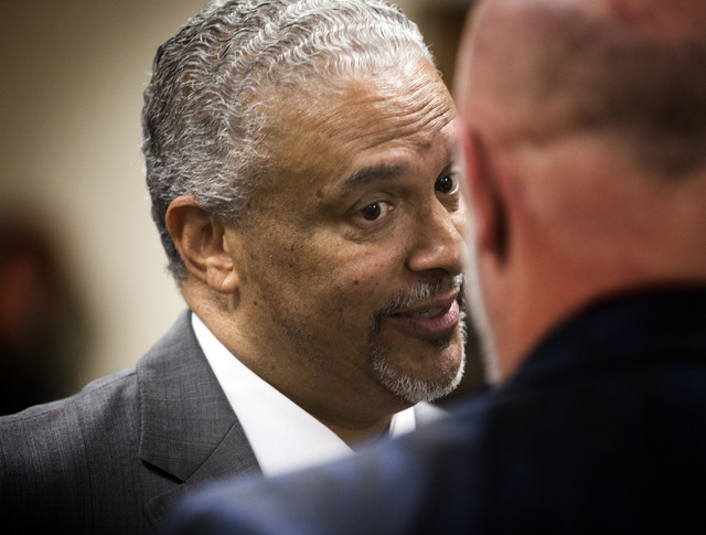 New UNLV men's basketball coach Marvin Menzies, left, talks to regent James Dean Levitt during the University of Nevada Board of Regents meeting to approve his contract on Friday, April 22, 2016.  ...