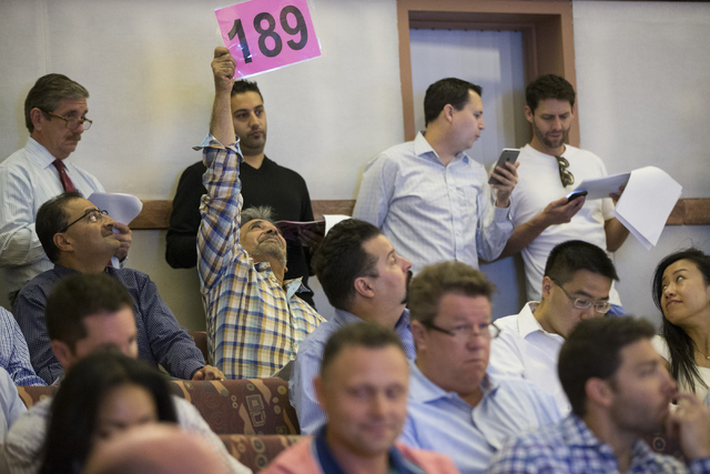 Khusrow Roohani, owner of Seven Valleys Realty and Construction, places a bid in a Bureau of Land Management land auction at the Clark County Commission chambers on Tuesday, April 26, 2016, in Las ...