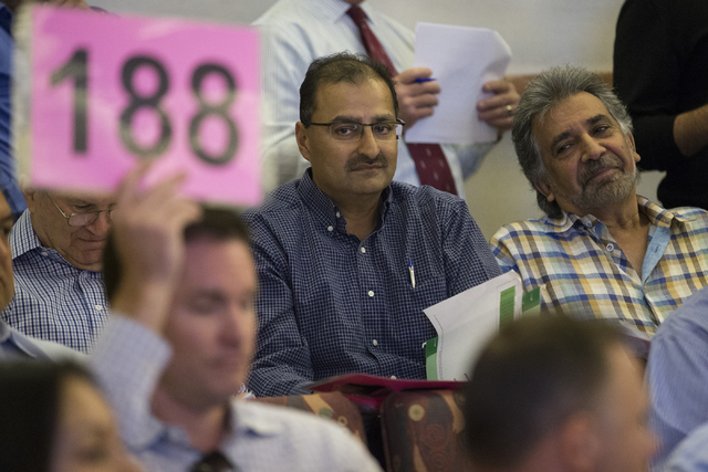 Manny Pattni, left, vice president of Lewis Management Corp., and Khusrow Roohani, owner of Seven Valleys Realty and Construction, look on during a Bureau of Land Management land auction at the Cl ...