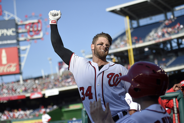 Washington Nationals' Bryce Harper pumps his fist as he takes a curtain call after he hit a grand slam during the third  inning of an baseball game against the Atlanta Braves, Thursday, April 14,  ...