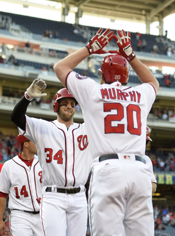 Washington Nationals' Bryce Harper (34) celebrates his grand slam with Daniel Murphy during the third inning of an baseball game against the Atlanta Braves, Thursday, April 14, 2016, in Washington ...