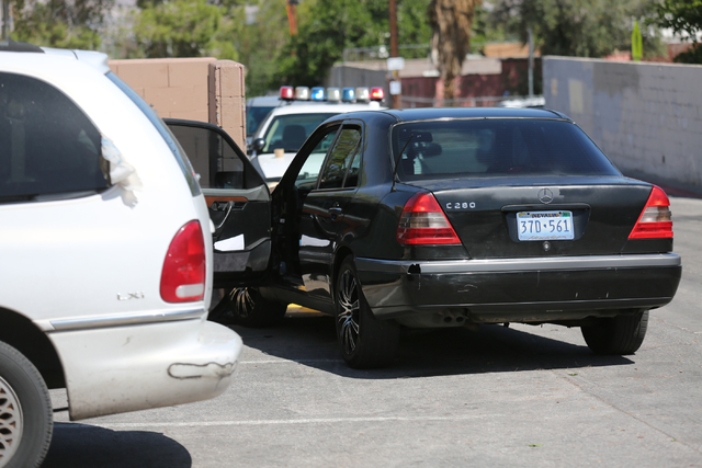 A black Mercedes is shown behind police crime scene tape at Harris Avenue near Bruce Street on Saturday, April 16, 2016, in Las Vegas. One person was taken into custody after a shooting on 13th St ...