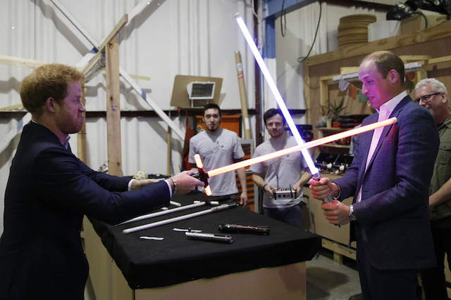 Britain's Prince William, right, and Prince Harry use light sabres during a tour of the Star Wars sets at Pinewood studios. (AP/Adrian Dennis)