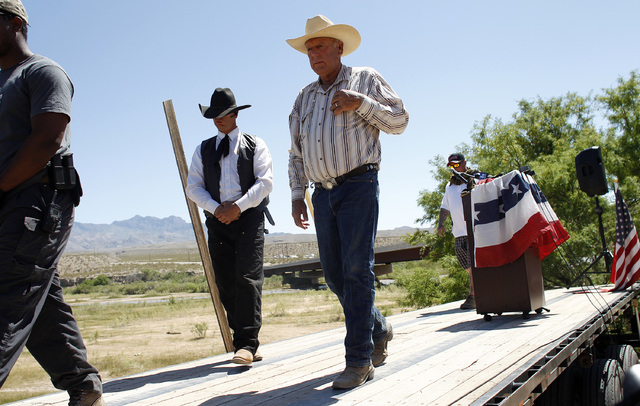 Rancher Cliven Bundy, right, walks of stage after speaking at a press conference near Bunkerville, Nev. Thursday, April 24, 2014. (John Locher/Las Vegas Review-Journal)
