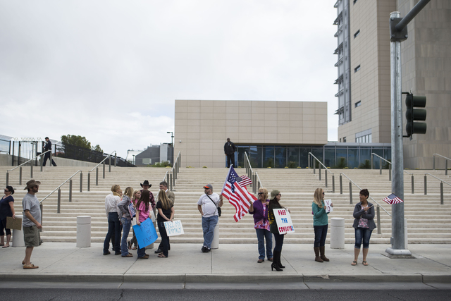 People, including Doug Knowles of Pahrump, center, protest outside of the Lloyd George Federal Building ahead of an arraignment for Ammon and Ryan Bundy, among others, in Las Vegas on Friday, Apri ...